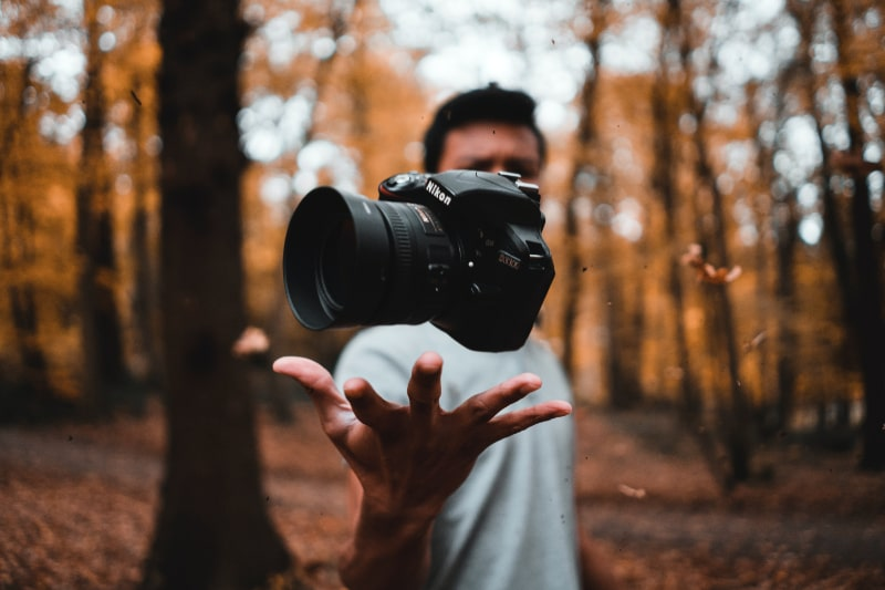 photography: man throwing camera in the air